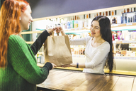 Smiling shop assistant handing over paper bag to customer in a cosmetics shop - WPEF00665