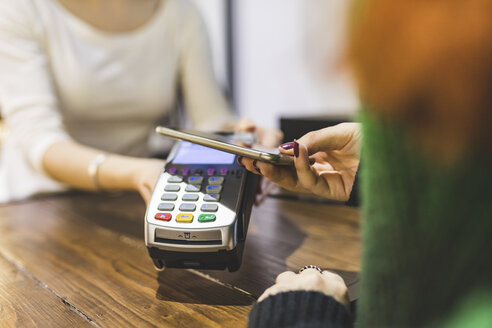 Customer paying cashless with smartphone in a shop - WPEF00668