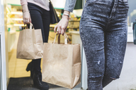 Close-up of two women leaving shop holding paper bags - WPEF00671