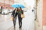 Two happy women shopping in the city on a rainy day - WPEF00674