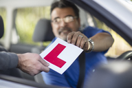 Driving instructor holding L sign in car - ZEF15778