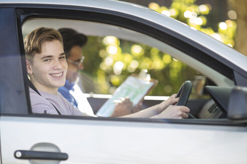 Portrait of smiling learner driver with instructor in car - ZEF15781