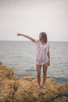 Young woman standing on a rock at the coast pointing her finger - ACPF00110