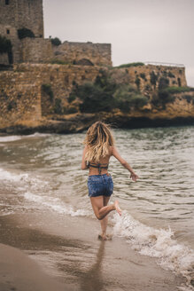 Rear view of young woman running on the beach - ACPF00116