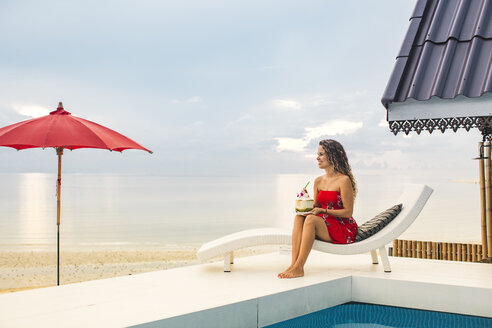 Thailand, Koh Phangan, happy woman sitting at poolside near the beach looking at distance - MOMF00474