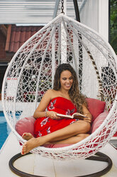 Thailand, portrait of smiling woman sitting in swing reading a book - MOMF00477