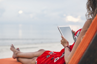 Thailand, Koh Phangan, woman sitting on sunlounger using digital tablet on the beach - MOMF00480