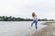Smiling woman splashing water in a river - UUF14446