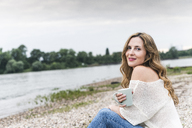 Smiling woman with cup of coffee sitting at the riverside - UUF14452