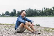 Laughing man sitting at the riverside looking sideways - UUF14458