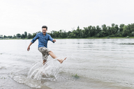 Laughing man splashing water in a river - UUF14464