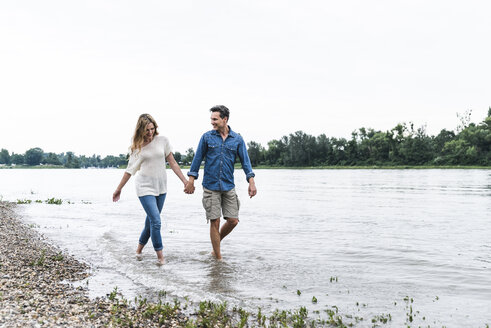 Happy couple wading in river - UUF14485