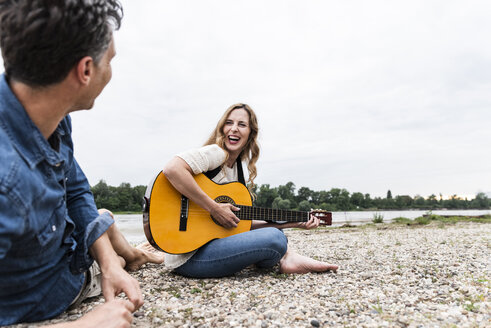 Happy woman with man at the riverside playing guitar - UUF14491
