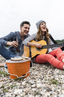 Happy couple with beer bottle, guitar and grill relaxing on pebble beach - UUF14506