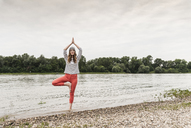 Woman practicing yoga in a river - UUF14512