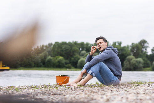 Man sitting at the riverside enjoying a fried sausage - UUF14521