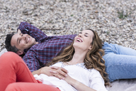 Happy affectionate couple lying on a blanket at pebble beach - UUF14527