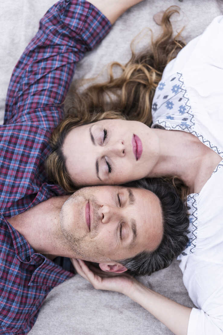 Affectionate couple with closed eyes lying on a blanket - UUF14533 - Uwe Umstätter/Westend61