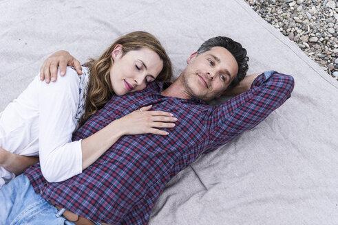 Affectionate couple lying on a blanket - UUF14536