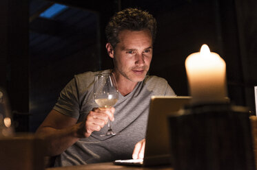 Man having glass of white wine looking at laptop - UUF14548