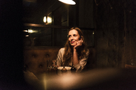 Smiling woman sitting at dining table looking sideways - UUF14551
