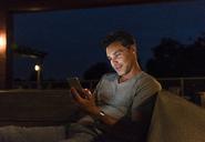 Man sitting in a dark illuminated room using cell phone - UUF14554