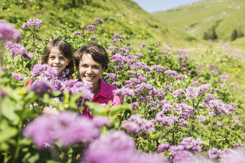 Mother and daughter hiding among wild flowers, Tyrol, Austria - CUF40428