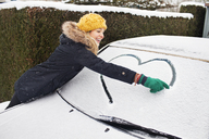 Woman drawing heart shape on snow covered windscreen - CUF40440