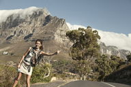 Young woman hitching from Table Mountain, Cape Town, South Africa - CUF40482