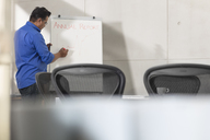 Businessman writing on whiteboard in conference room - ZEF15807