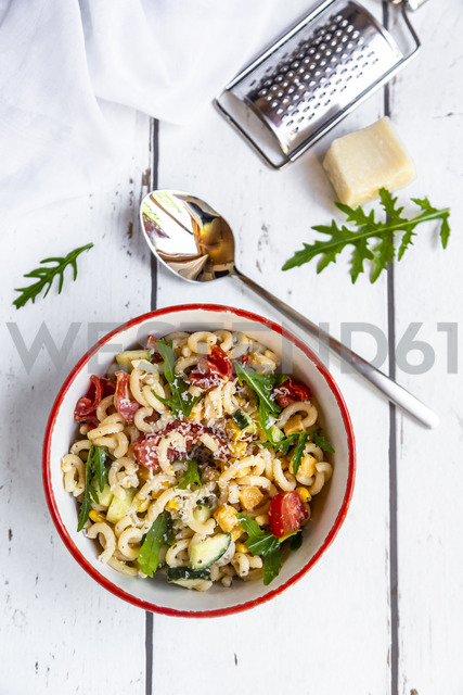 Bowl of noodle salad with corn, cucumber, tomatoes, rocket and grated parmesan - SARF03826