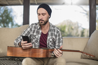 Young man at home sitting on couch with guitar using cell phone - ZEF15816