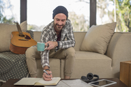 Smiling young man at home sitting on couch with guitar taking notes - ZEF15819