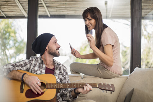 Young man at home sitting on couch playing guitar for woman - ZEF15825