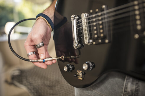 Close-up of man's hand plugging electric guitar - ZEF15828