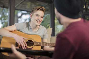 Musician teaching student how to play guitar - ZEF15834