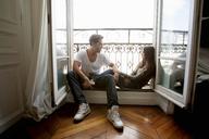 Couple sitting in windowsill - CUF40617