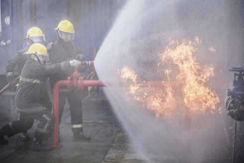 Three firefighters putting out fire in fire simulation training facility - CUF40677