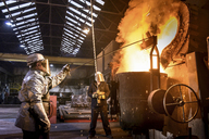 Workers pouring molten metal in foundry - CUF40695