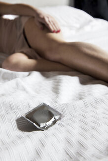 Close up of condom wrapper on bed - CUF40872