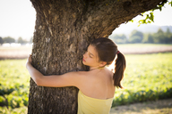 Girl hugging tree in summer - LVF07257