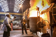 Workers pouring molten metal in foundry - CUF40977