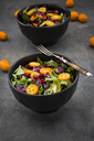 Bowl of mixed green salad with red cabbage, kumquat and pomegranate seeds - LVF07262