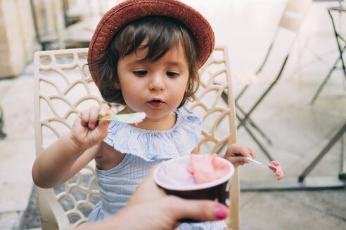 Cute toddler girl eating an ice cream held by her mother - GEMF02113