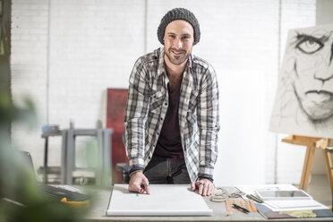 Portrait of confident artist standing at his desk in studio - ZEF15866