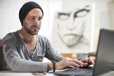 Artist using laptop in studio - ZEF15869