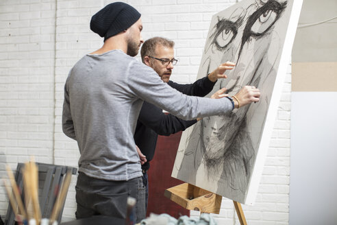 Artist discussing drawing with man in studio - ZEF15872