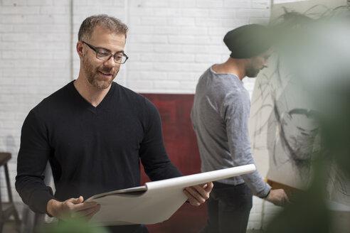 Smiling man looking at sketchbook in artist's studio - ZEF15875