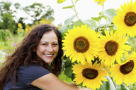 Portrait of young woman and sunflowers in allotment - CUF41108