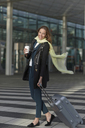 Young woman at airport with wheeled case and coffee - CUF41189